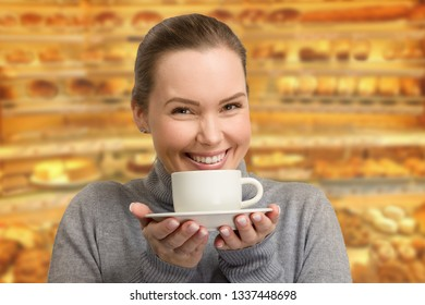 Woman with a cup of coffe in front of a cafe