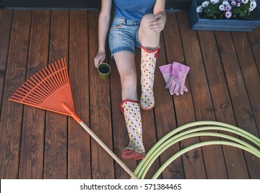 Woman with cup of coffee and gardening tools sitting on a patio wooden deck resting after working in the garden
