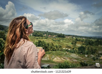 Woman with a cup of coffee on the cafe veranda near the rice terraces on Bali, Indonesia