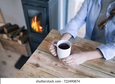 Woman with cup of coffee sitting by the fireplace and wooden table