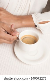 Woman with cup of coffee. Top view of woman holding a cup of coffee