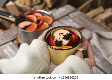 Woman with cup of delicious mulled wine at table, closeup