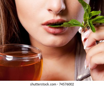 Woman with cup of fresh tasty black tea