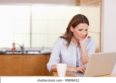 Woman with cup and her notebook in the kitchen