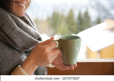 Woman with cup of tasty coffee outdoors on winter morning, closeup