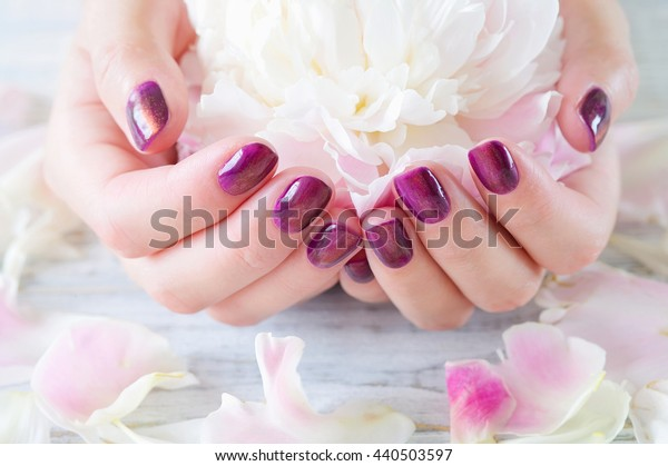Woman cupped hands with manicure holding pink flower