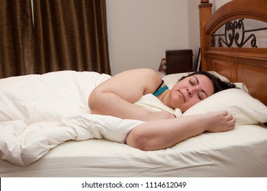 A woman curled in snuggled in her warm bed asleep