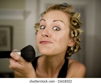 Woman in Curlers Applying Makeup with a Brush