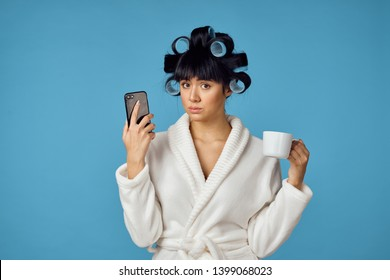 woman with curlers drinks tea and looks into the phone