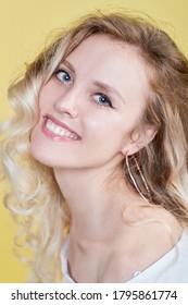 Frau mit lockig schönen Haaren auf gelbem Hintergrund. Mädchen mit Schönheit ein angenehmes Lächeln. Kurze Haare