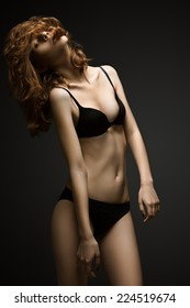 Woman with curly hair in black underwear on black background
