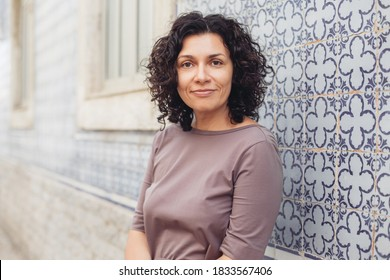 A woman with curly hair in Portugal. A wall with traditional Portuguese tiles
