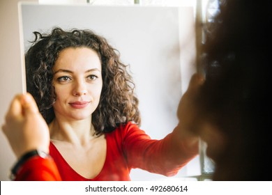 Woman with curly hair standing in front of  large mirror and smiling
