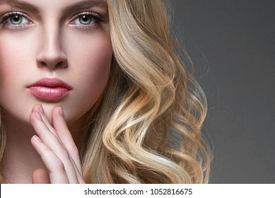 Woman with Curly long hair blonde young model. Beauty girl with perfect hairstyle. Studio shot.