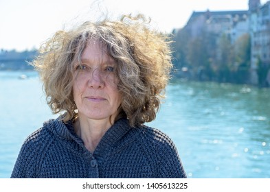 Woman with curly tousled hair outdoors on a bridge standing with her back to the water looking thoughtfully off to the side backlit by the sun