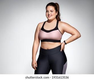 Frau mit kurviger Figur in modischer Sportbekleidung auf grauem Hintergrund. Sportmotivation und gesunder Lebensstil