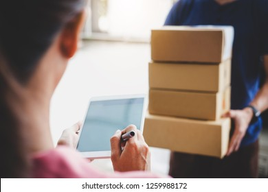 Woman customer appending signature in digital tablet and receiving a cardboard boxes parcel from delivery service courier, Home delivery service and working with service mind.