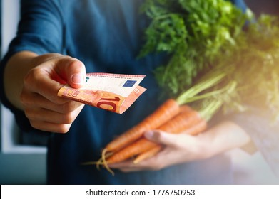 Woman customer buying and holding a bunch of carrots and pay to farmer. Fresh produce at the local farmers market. Healthy eating Concept.