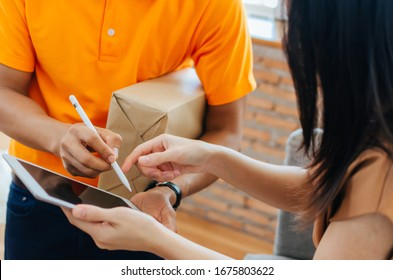 woman customer get a pen form delivery service man in orange uniform for signature in digital mobile tablet receiving parcel post box from courier at home, express delivery and shopping online concept
