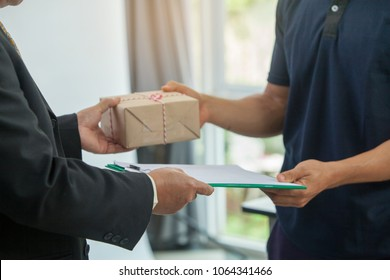 woman customer hand accepting receiving a package  from a deliveryman in blue uniform at home.postal and delivery package through a service,courier service concept,