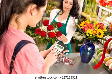 Woman customer paying flowers shop credit card florist roses