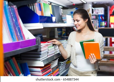 Woman customer picking various notebooks for writing in stationary department