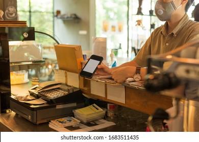 Femme cliente avec masque de protection payant la facture par téléphone portable au café
