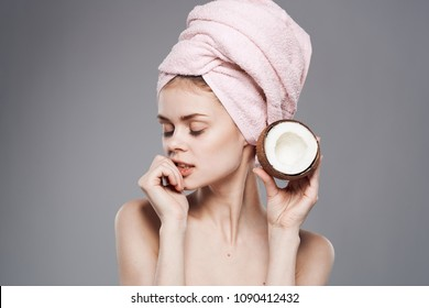 woman with a cut coconut in her hand and with a pink towel on her head