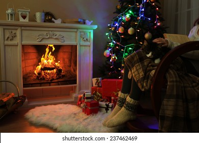 Woman and cute cat sitting on rocking chair and read the book, in the front of the fireplace