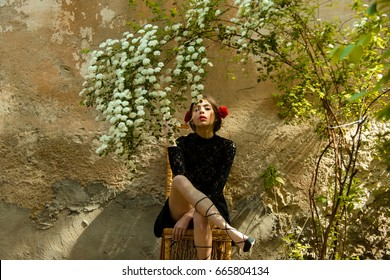 woman or cute girl, fashionable young model with red lips, roses in hair in black lace dress sitting on wicker chair under bush with white blossoming flowers on beige outdoor wall. Spring