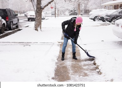 Woman in cute pink hat shovelling / shoveling snow