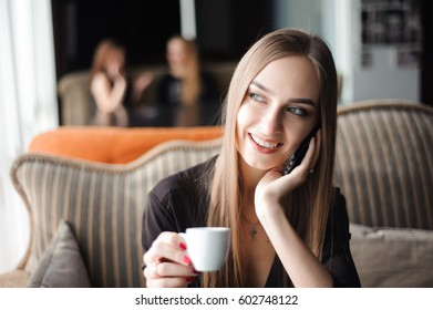 a woman with cute smile having mobile phone conversation while resting after work day in cafe