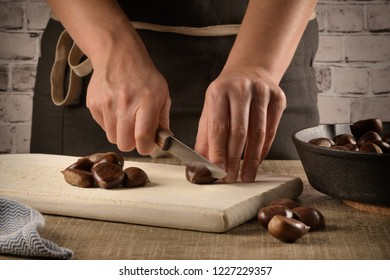 Woman cuts chestnuts on wooden cutting board.