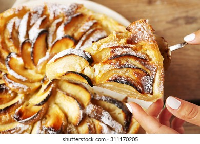Woman cuts homemade apple cake, close-up