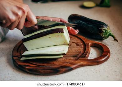A woman cuts with a knife raw eggplant on a cutting board.