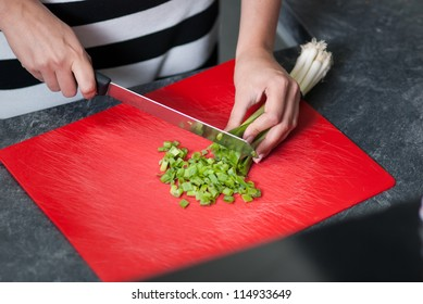 Woman cuts leek on a kitchen bench in the kitchen