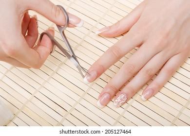 woman cuts nails scissors, close up.