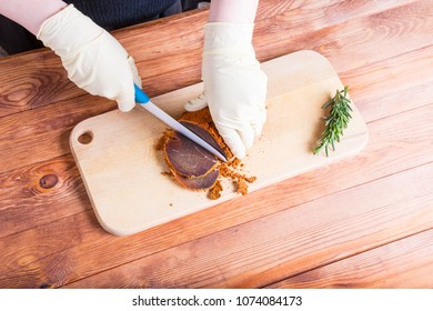 Woman cuts a piece of beef pastourma by ceramic knife on a timbered table