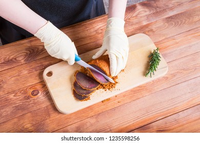 Woman cuts a piece of beef pastourma by ceramic knife on a wooden table