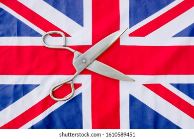 A woman cuts with scissors the British flag in protest.