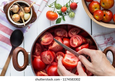 Woman cuts tomatoes for preserves, cooking and food concept, top view