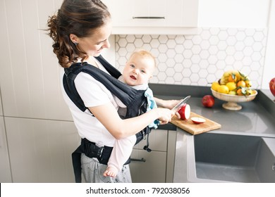 Woman cutting an apple with child in baby carrier ergo backpack