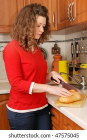 woman cutting bread at kitchen