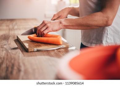 Woman cutting carrot on cutting board
