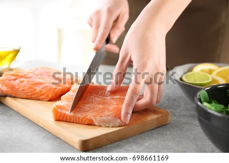 Woman cutting fresh salmon fillet on wooden board
