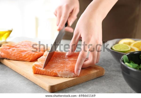 Woman cutting fresh salmon fillet on wooden board