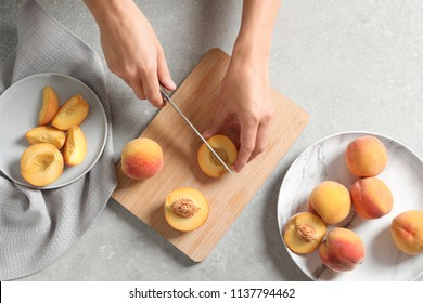 Woman cutting fresh sweet peaches on table, top view