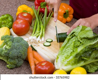 A woman cutting up fruits and vegetables