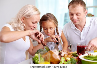Woman cutting meat at dinner table