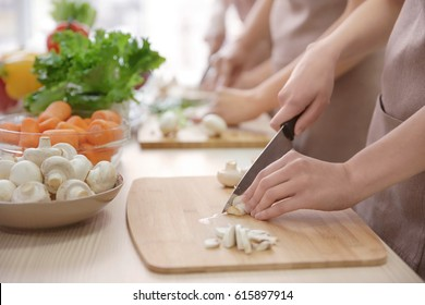 Woman cutting mushrooms at cooking classes